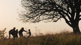 Precipitações felizes das crianças nas mãos dos pais Os pais abraçam suas crianças no prado filme