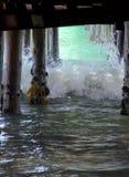 Precipitación de las olas oceánicas adentro debajo del embarcadero fotografía de archivo