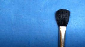 Precipitación del maquillaje en fondo azul imagenes de archivo