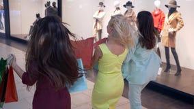 Precipitación del shopaholics de las chicas jóvenes a la venta en el descuento en tiendas costosas de la moda en Black Friday metrajes