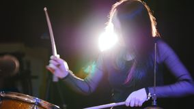 Precipitarsi la ragazza con il batterista della percussione dei capelli neri comincia giocare i tamburi video d archivio