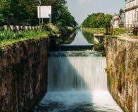 Precipiti a cascata su una serratura al Naviglio Pavese, un canale che collega la città di Milano con Pavia, Italia, fotografie stock