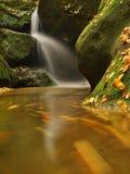 Precipiti a cascata sulla piccola torrente montano, l'acqua sta investendo i massi muscosi dell'arenaria e le bolle creano sull'ac Immagini Stock