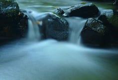 Precipiti a cascata sulla torrente montano, l'acqua sta investendo i massi del basalto e le bolle creano sull'acqua lattea livella Fotografia Stock