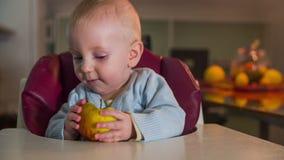 Precis fött barn med halva ett äpple i hans händer stock video