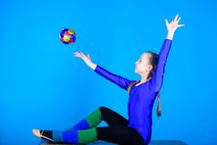 Precis flyga gymnastik Lycklig barnidrottsman med bollen Sport och hälsa Kondition bantar Energi Akrobatikidrottshallgenomkörare royaltyfri foto