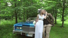 Precis gift bröllopparbrud och brudgum som är förälskade nära den brud- bilen för tappning arkivfilmer