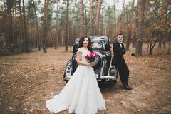Precis gift par i den lyxiga retro bilen på deras bröllopdag royaltyfri foto