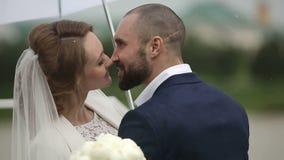 Precis gift par i regnig dag på terrassen med paraplyet långsam rörelse arkivfilmer