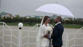 Precis gift par som går i regnig dag på terrassen med paraplyet lager videofilmer