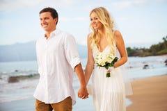 Precis gift par som går på stranden på solnedgången royaltyfri foto