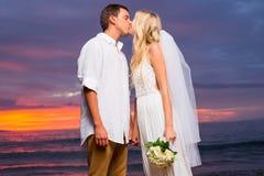 Precis gift par som kysser på den tropiska stranden på solnedgången royaltyfri fotografi