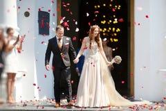 Precis gift par under ett regn av blommakronblad fotografering för bildbyråer