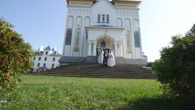 Precis gift parbrud och brudgum nära kyrkan lager videofilmer