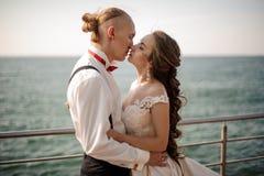 Precis gift pojke och flicka som kysser sig på pir på sjön arkivfoton