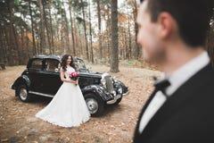 Precis gifta lyckliga par i den retro bilen på deras bröllop Arkivfoton