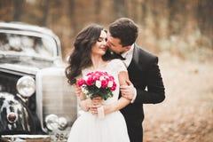 Precis gifta lyckliga par i den retro bilen på deras bröllop Arkivbild