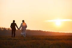 Precis gifta paret går in mot en solnedgång som rymmer deras handsi Arkivfoto