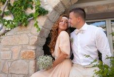 Precis gifta paret omfamnade lantlig stilweddin för bruden och för brudgummen Arkivbilder