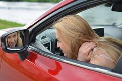 Precis kontrollera makeup, ung flicka i en bil royaltyfri fotografi