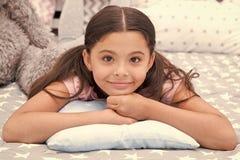 Precis koppla av Flickabarnet l?gger p? kudden i hennes sovrum Ungen f?rbereder sig att g? att b?dda ned Stilfull inre f?r angen? royaltyfri foto