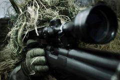 Precise as a Sniper. A sniper wearing a camouflage grass-coat is aiming with a sniper rifle Stock Image