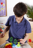 Precise boy with toys. A little boy focused on playing with blocks Stock Images