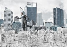 Precise businessman in suit running with phone. Attractove businessman in suit running with phone in hand among flying letters with cityscape on background Stock Image