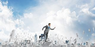 Precise businessman in suit running with phone. Businessman in suit running with phone in hand among flying letters with cloudly sky on background. Mixed media Royalty Free Stock Image