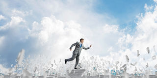 Precise businessman in suit running with phone. Businessman in suit running with phone in hand among flying letters with cloudly sky on background. Mixed media Royalty Free Stock Images