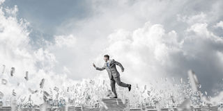 Precise businessman in suit running with phone. Businessman in suit running with phone in hand among flying letters with cloudly sky on background. Mixed media Stock Photos