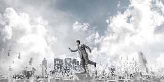 Precise businessman in suit running with phone. Businessman in suit running with phone in hand among flying letters with cloudly sky on background. Mixed media Stock Photography