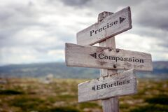 Free Precise Compassion Effortless Text Engraved On Old Wooden Signpost Outdoors In Nature Stock Image - 182605701