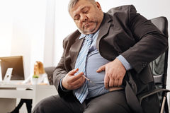 Precise feeble employee making an injection. Daily routine. Middle aged unhealthy chubby men holding a syringe with his medicine and preparing himself for royalty free stock image