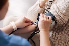 Precise fokuserade doktorn som erhåller blodtryckmätningar arkivbilder