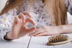 Precise mais vitaminas, mulher com problemas do cabelo, cabelo perdido no pente fotos de stock royalty free