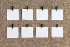 Precisely aligned rows of blank memo pads. Hanging from wooden clothes pegs over a textured woven burlap background in a concept of organization Stock Image