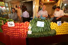 Precisely arranged piles of tomatoes, cucumbers lemons and peppers in front of grocers at bazaar market, Iraq, Middle East