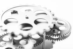 A precision machinery of silver colored gears in an  background Royalty Free Stock Photos