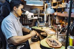 Precision work carried out by jeweler. In workshop stock images