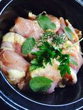 Precooked Crockpot Chicken. Chicken thighs topped topped with herbs of rosemary, parsley and sage. Seasoned with salt, pepper, chicken stock and apple cider Royalty Free Stock Images