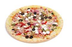 Precooked pizza med bacon, oliv, körsbärsröda tomater, getost Arkivbild