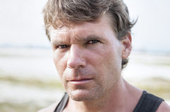 Predator eyes. Closeup portrait of rugged Caucasian man with stern bold facial expression, distinct features, and intense predator eyes in undefined outdoor Royalty Free Stock Photography