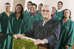 Predicador confiado que se coloca en el púlpito con coro en fondo Fotografía de archivo
