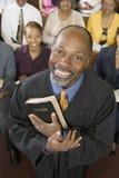 Predicador que sostiene la Sagrada Biblia con la congregación que se sienta en iglesia Fotos de archivo libres de regalías