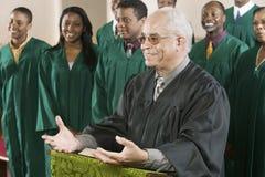 Predicatore che sta al quadro di comando con il coro nel fondo alla chiesa Immagini Stock Libere da Diritti