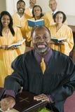 Predicatore con la bibbia mentre coro che sta nel fondo alla chiesa Immagini Stock Libere da Diritti