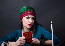 Predicting the future, access to the astral. Young beautiful fortune teller wondering on the Tarot cards. Predicting the future, access to the astral Royalty Free Stock Photography