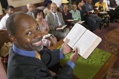 Predikant på den öppna bibeln för altareinnehav framme av sikten för hög vinkel för kongregationstående royaltyfria foton