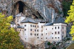 Predjamski grad in Postojnska jama v gore jame Slovenija stock photo